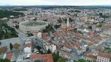 Aerial footage of stunning amphitheatre, a historic structure dating back from the Roman empire in central Pula, a popular tourist destination in Istria, Croatia - 211654907