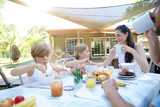 Family having breakfast in summer morning - 211656396