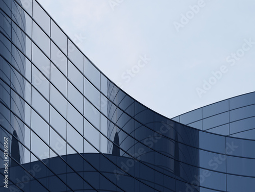 Naklejka 3D stimulate of high rise curve glass building and dark steel window system on blue clear sky background,Business concept of future architecture,lookup to the angle of the corner building.3d rendering
