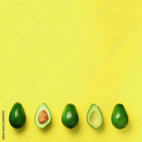 Organic avocado with seed, avocado halves and whole fruits on yellow background. Top view. Square crop. Pop art design, creative summer food concept. Green avocadoes pattern in minimal flat lay style. - 211663545