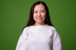 Young Chinese woman against green background