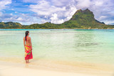 Tahiti luxury travel beach vacation woman walking in polynesian cover-up skirt beachwear on idyllic paradise island in French Polynesia. Red traditional clothes, bikini and flower girl. - 211671917