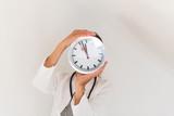 Arzt mit einer Uhr in den Händen - 211671975