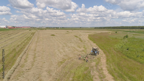 Fotobehang Trekker Aerial, view agricultural machinery with wheeled rake makes ranks beveled hay.Tractor which is lining up dried grass getting it ready for pickup so it can be used as animal fodder summer day.