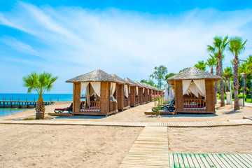 Wooden beach pavilions on the shore of a sandy beach