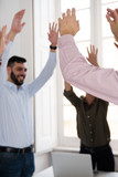 Corporate group celebrating with raised hands - 211675332