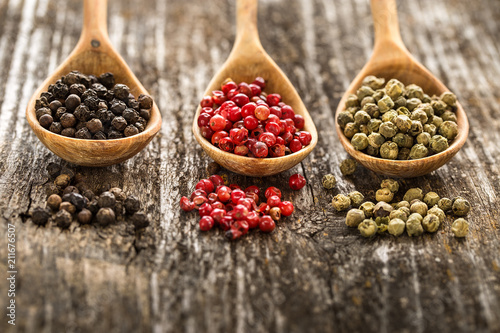 Different pepper in a wooden spoons on wooden table. - 211676507