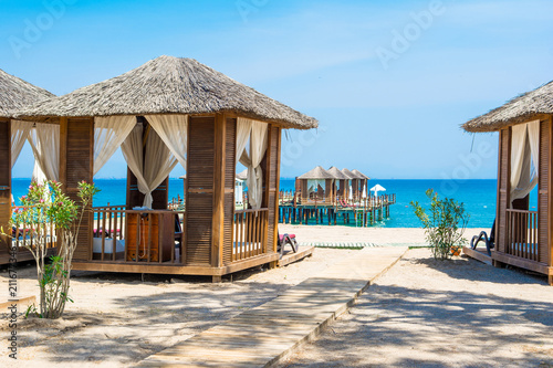 Wooden beach pavilions on the shore of a sandy beach - 211677346