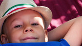 Young boy resting in hammock in summer sunny day. Close up portrait of child - 211681179