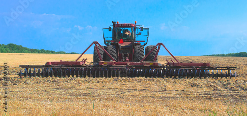 Aluminium Trekker red tractor for harvesting in the midst of the summer season, produces disk field