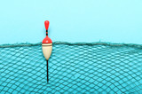 Fishing net with homemade bobber on blue background. Picture with space for your text. - 211694720