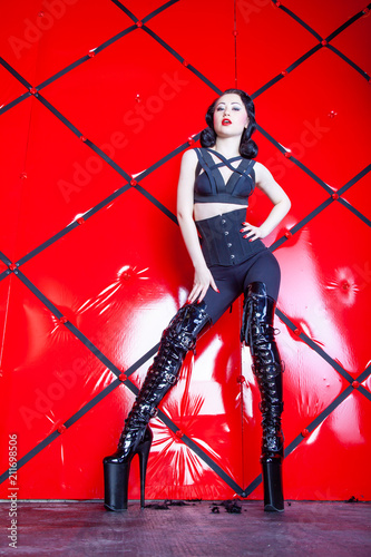 Leinwanddruck Bild hot pin up kinky woman wearing black harness and shiny fetish thigh high boots on red background alone