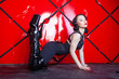 Leinwanddruck Bild - hot pin up kinky woman wearing black harness and shiny fetish thigh high boots on red background alone