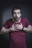 Shocked and appalled young man expression, studio, black background - 211700932