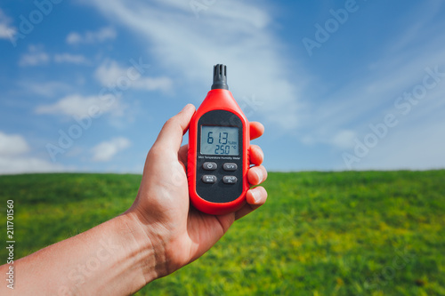 Leinwanddruck Bild portable thermometer in hand measuring outdoor air temperature and humidity