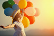 Leinwanddruck Bild - happy woman with balloons at sunset in summer