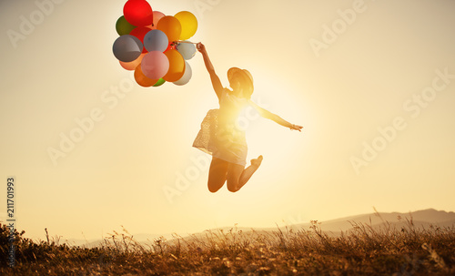 Leinwanddruck Bild happy woman with balloons at sunset in summer