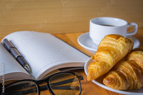 Poster Croissant, coffee and notebook on wodd table