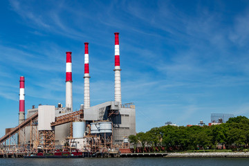 Power plant smoke stack towers contrast against blue sky background and green trees below