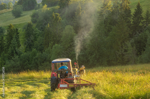 Aluminium Trekker haymaking in the mountains, tractors with mowers cutting the meadows in the Polish mountains