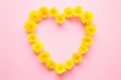Heart shape is created from bright yellow dandelion heads on light pastel pink background. Love concept. Mockup for positive ideas. Empty place for delicate, emotional or sentimental text or quote.