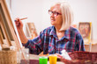 Elderly woman is painting in her home. Retirement hobby. - 211736360