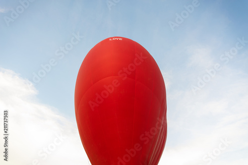 Red hot air balloon with inscription Love. Love, honeymoon and romantic travel concept