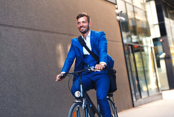 Young businessman going to work with his bicycle.