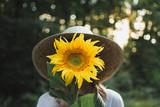 Woman hiding behind sunflower