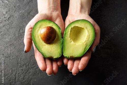 Leinwanddruck Bild Fresh avocado fruit in girl hands. The concept of healthy eating. Food photography