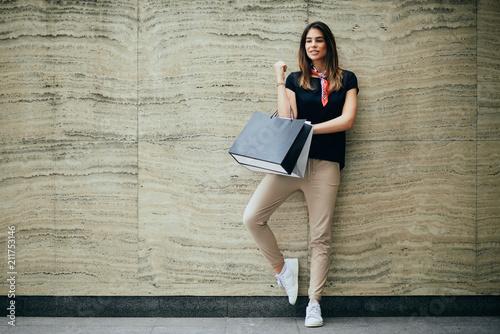 Kobiety pozycja przeciw ścianie i mieniu papierowe torby. Koncepcja zakupy