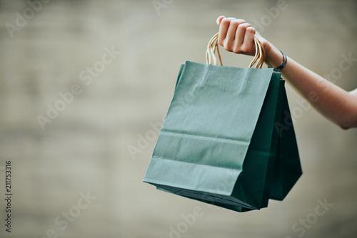 Ręka trzyma torba na zakupy. Ściana w tle.