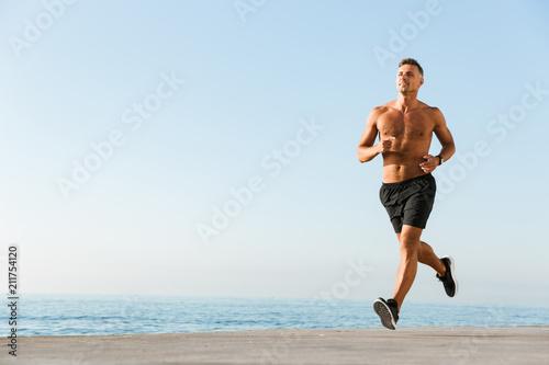 Happy shirtless sportsman running - 211754120