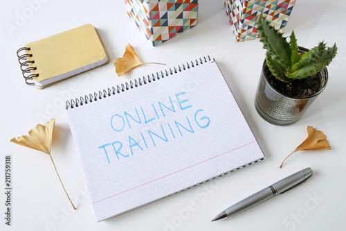 Leinwanddruck Bild online training written in a notebook on white table
