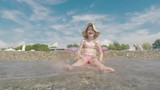 A cool girl in a pink bathing suit and wearing a broad-brimmed hat is having fun on the seaside, playing with the waves - 211765769
