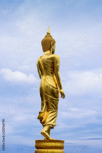 Fotobehang Boeddha The backside of the standing Buddha statute at Phrathat Khao Noi temple, Nan Province, Thailand, with blue sky and white cloud background