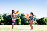 Two little girls blowing upon colorful pinwheels. - 211768502