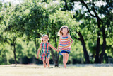 Two little smiling girls running on the grass, holding hands - 211768527