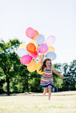 Happy girl in running with a bunch of balloons - 211768721