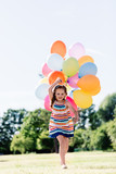 Happy little girl running with a bunch of colorful balloons - 211768764