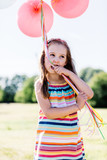 Little girl chewing balloon strings in her mouth - 211768907