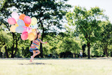 Little girl running fast with a bunch of colorful balloons - 211769317