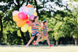 Two little happy girls running with a bunch of colorful balloons.