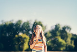 Little girl blowing soap bubbles in the park. - 211769743