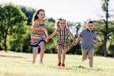 Two little girls and a boy running on the grass field. - 211769956