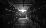 Underground concrete utility tunnel network of water pipeline with light at the end. Black and white - 211771104