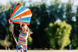 Smiling little girl playing with a colorful kite in the park. - 211771328