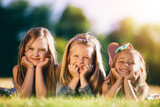 Three smiling little girls laying on the grass in the park. - 211771545