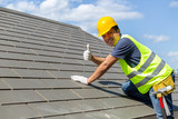 Asian tile roofing workers, smiling at the camera, lifted their thumbs to indicate the stability of the roof. - 211771736