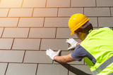 Roof repair, worker with white gloves replacing gray tiles or shingles on house with blue sky as background and copy space, Roofing - construction worker standing on a roof covering it with tiles. - 211771744